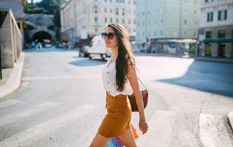 Vintage toned street style portrait of a young brunette woman, walking on the streets of Triest, Italy, in the summertime. She is wearing a casual skirt and a shirt, having a brown leather vintage purse, going shopping.